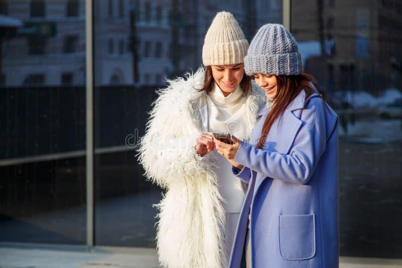 笑和分享在一个巧妙的电话的两个滑稽的妇女朋友社会媒介录影户外 免版税库存图片