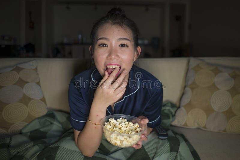 笑和吃玉米花的年轻美好的愉快和快乐的亚洲中国妇女看着电视喜剧电影或热闹的展示 库存照片