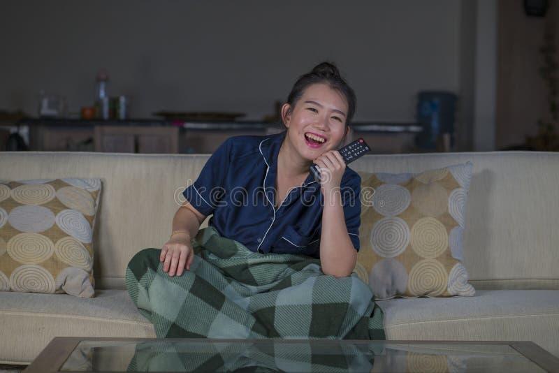 笑和吃玉米花的年轻美好的愉快和快乐的亚洲中国妇女看着电视喜剧电影或热闹的展示 免版税库存照片