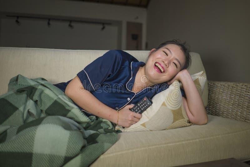 笑和吃玉米花的年轻美好的愉快和快乐的亚洲中国妇女看着电视喜剧电影或热闹的展示 免版税库存图片