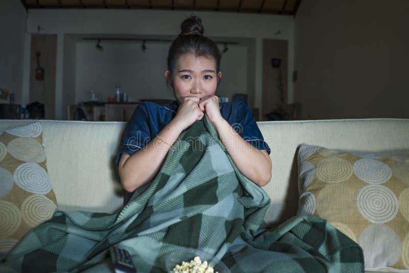 笑和吃玉米花的年轻美好的愉快和快乐的亚洲日本妇女看着电视喜剧电影或热闹的展示 免版税库存图片