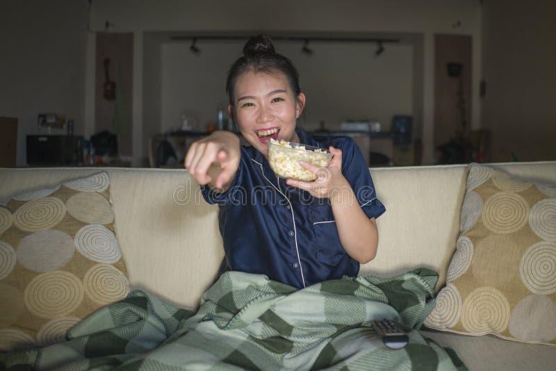笑和吃玉米花的年轻美好的愉快和快乐的亚洲日本妇女看着电视喜剧电影或热闹的展示 图库摄影
