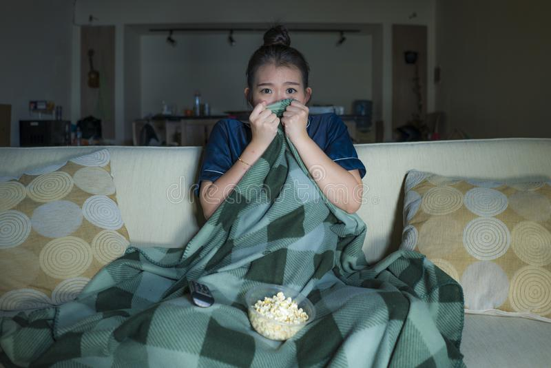 笑和吃玉米花的年轻美好的愉快和快乐的亚洲日本妇女看着电视喜剧电影或热闹的展示 免版税库存照片