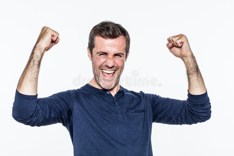 笑和呼喊为成功和满意的激动的年轻人 免版税库存照片