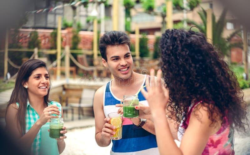 笑和喝在夏天党的青年人 免版税库存照片