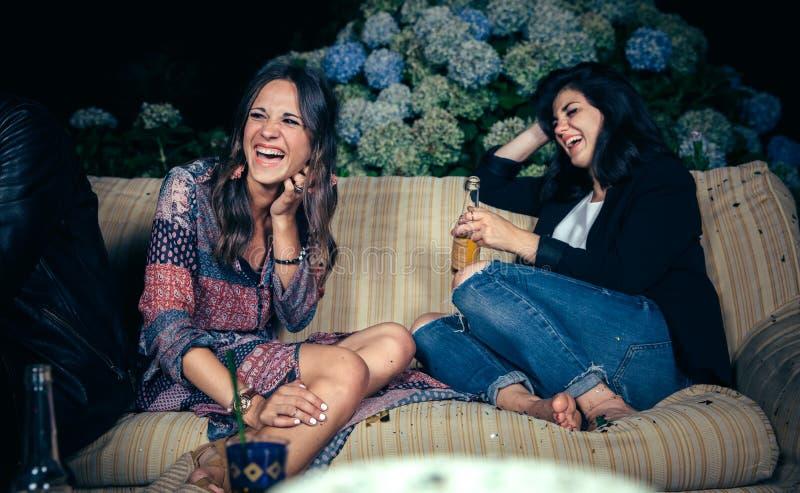 笑和喝在a的愉快的妇女朋友 库存图片