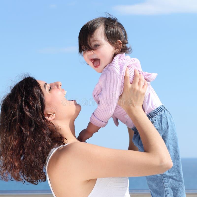 笑和培养她的女儿的俏丽的妈咪 免版税库存图片