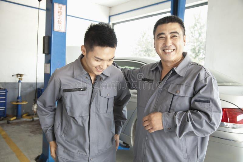 笑和微笑在工作的两位车库技工 免版税库存照片