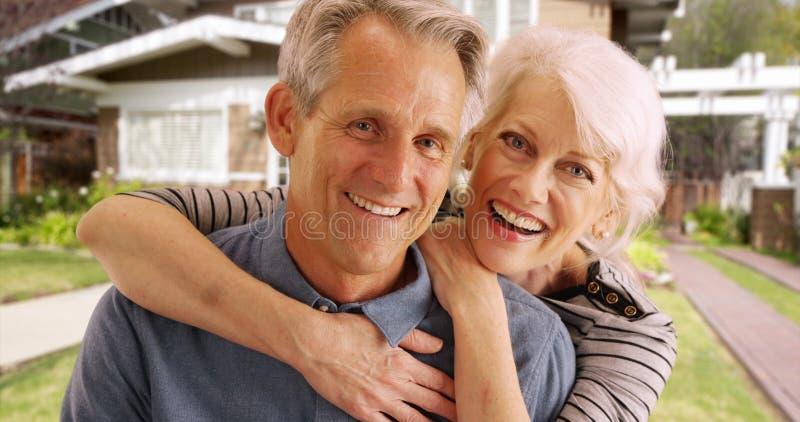 笑和微笑在他们的房子前面的愉快的资深夫妇 库存图片