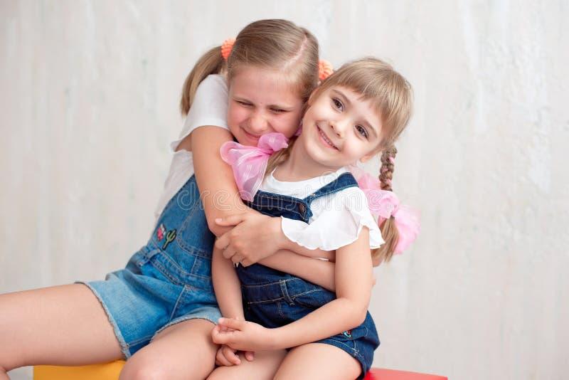 笑和拥抱的两个可爱的妹 免版税库存照片