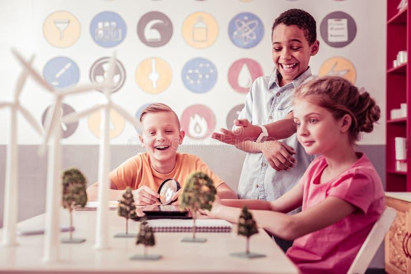 笑和指向在模型的满足的非裔美国人的男孩 免版税库存照片