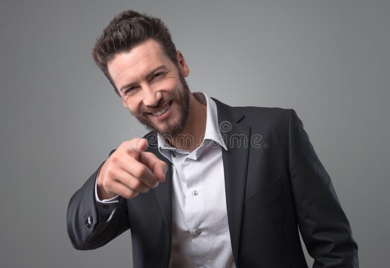 笑和指向手指的愉快的商人 库存照片
