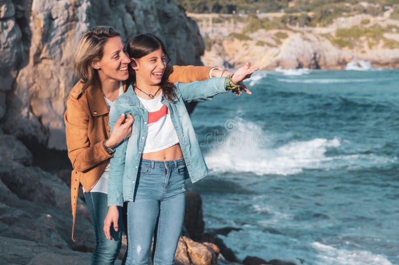 笑和指向某事的母亲和十几岁的女儿在地中海 库存照片