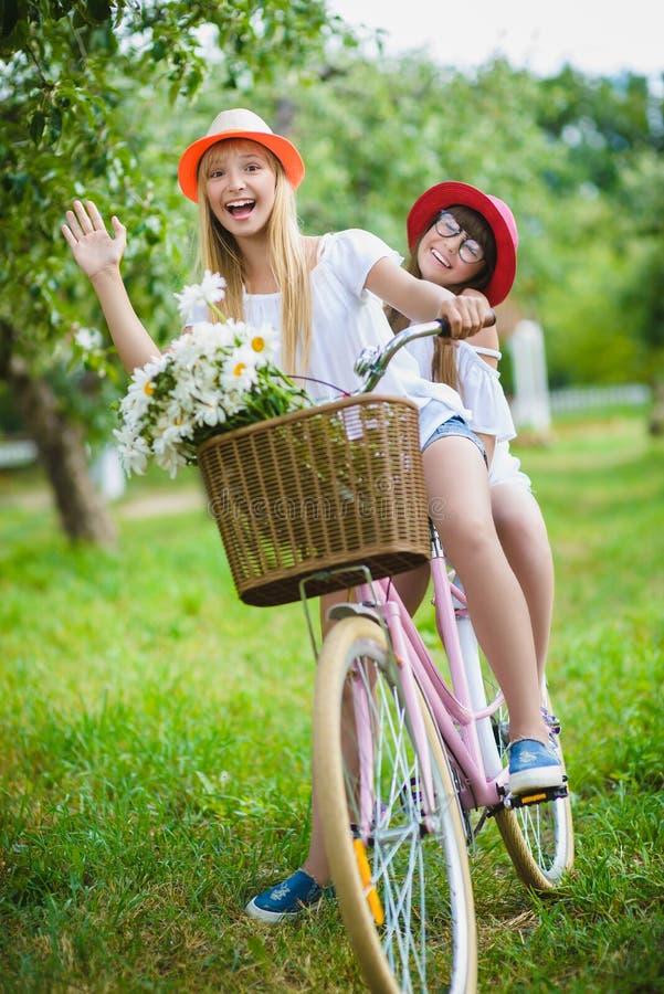 笑和摆在为与自行车的照相机的两个美丽的愉快的行家女孩 图库摄影
