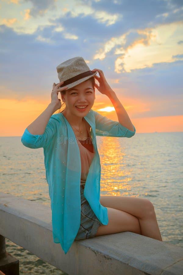 笑和放松w的年轻美丽的亚裔妇女画象  免版税库存图片