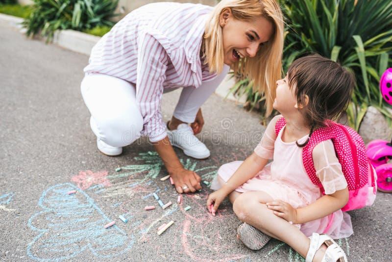 笑和画与在边路的五颜六色的白垩的愉快的女孩和母亲的图象 一起白种人女性戏剧 库存图片