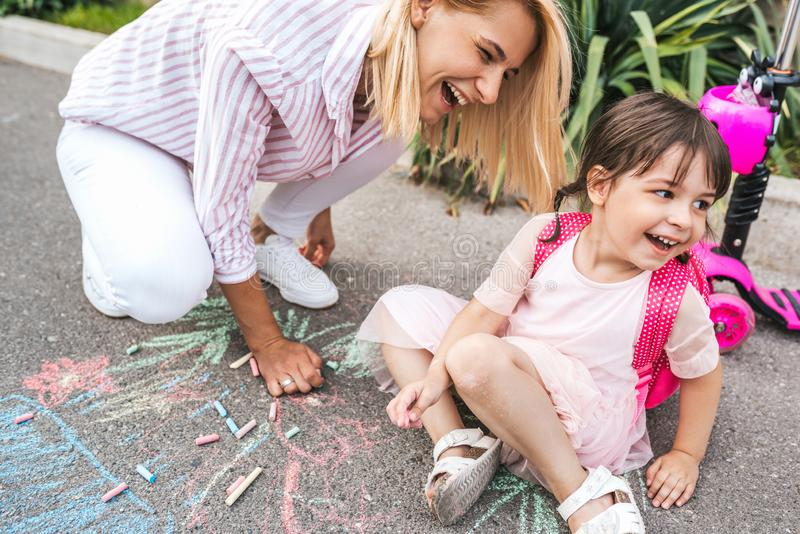 笑和画与在边路的白垩的愉快的女孩和母亲的水平的图象 一起白种人女性戏剧 免版税库存照片