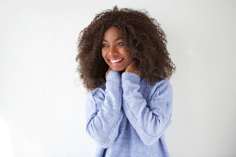 笑和看反对白色背景的愉快的年轻非洲妇女画象  免版税图库摄影