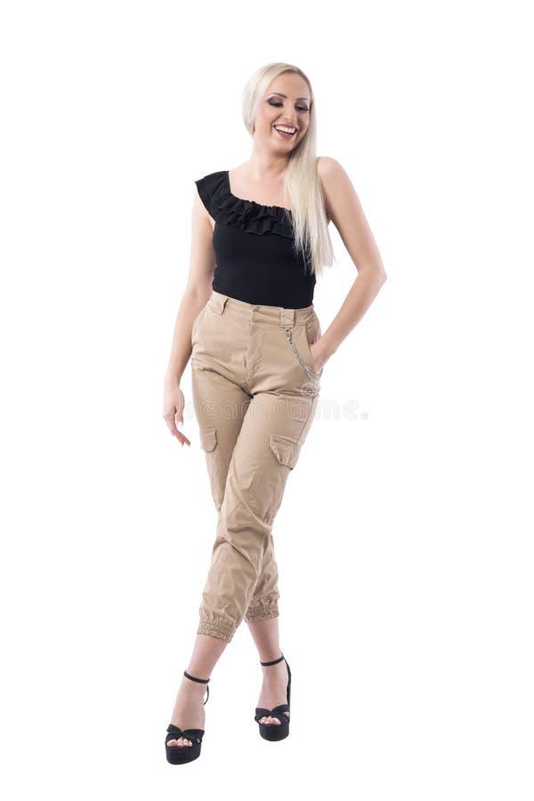 笑和看在佩带的奶油色颜色裤子下的惊人的白肤金发的迷人的妇女 库存图片
