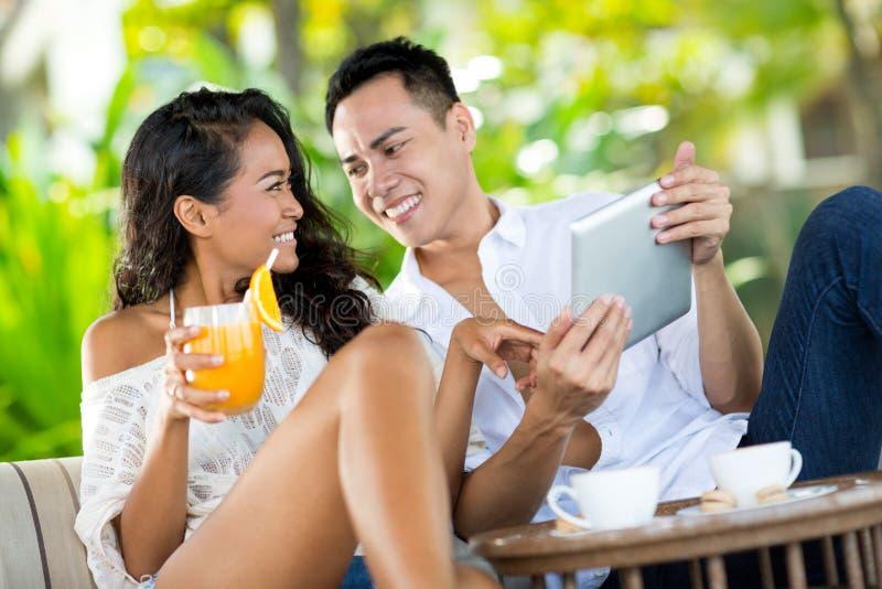 笑和看片剂个人计算机的年轻夫妇 库存照片