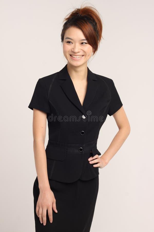 笑和看远离照相机的年轻亚裔夫人 免版税库存图片