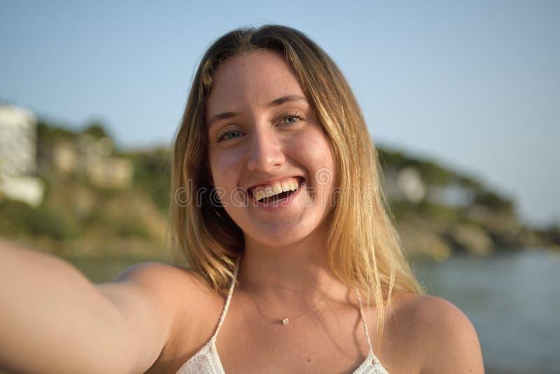 笑和采取在海滩的女孩的接近的画象selfie 库存照片
