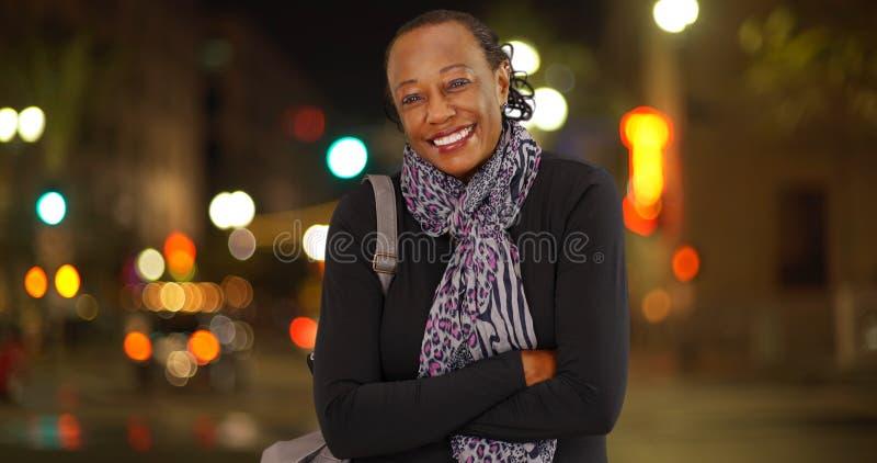 笑在一个繁忙街角的冷气候的一名更老的非裔美国人的妇女的画象 免版税库存图片