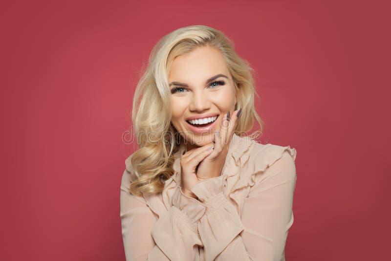 笑在五颜六色的明亮的桃红色背景的美丽的年轻愉快的妇女 情感摆在正随风飘飞的雪木头的时装模特儿 传神表情 免版税库存照片