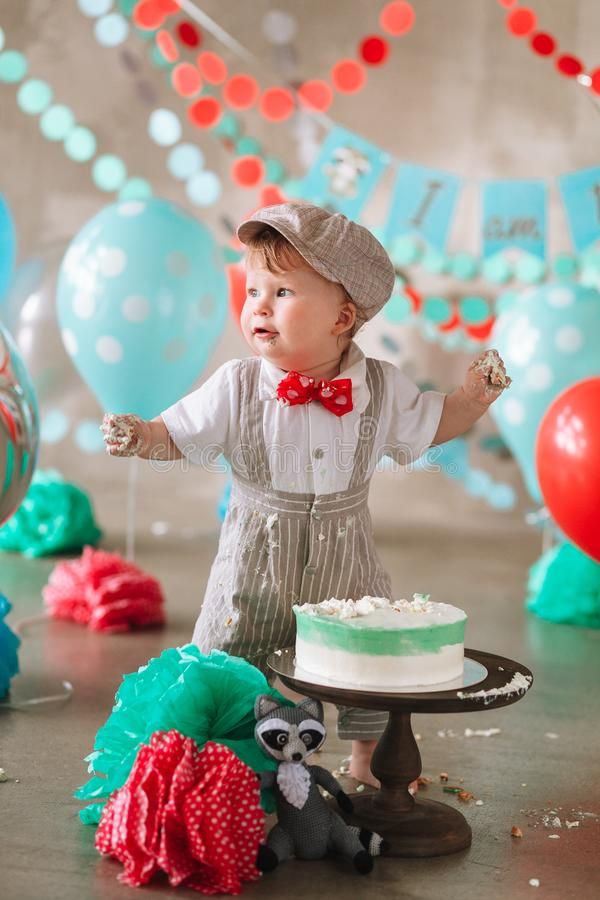 笑在他的第一生日蛋糕抽杀的滑稽的男婴 杂乱肮脏的手 免版税图库摄影