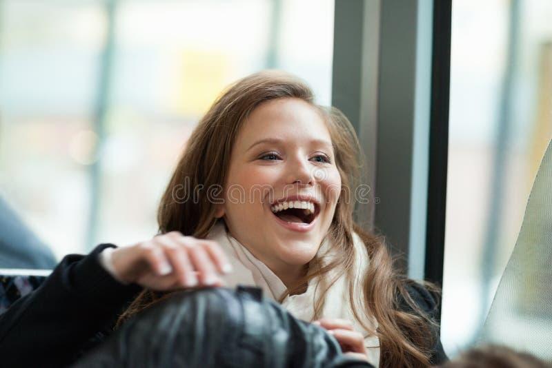 笑在公共汽车上的少妇 免版税库存照片