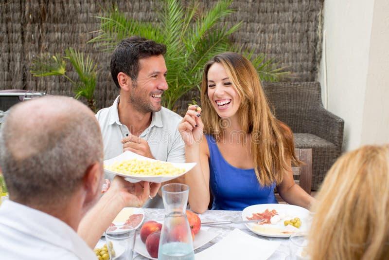 笑在家庭午餐期间的夫妇 免版税图库摄影