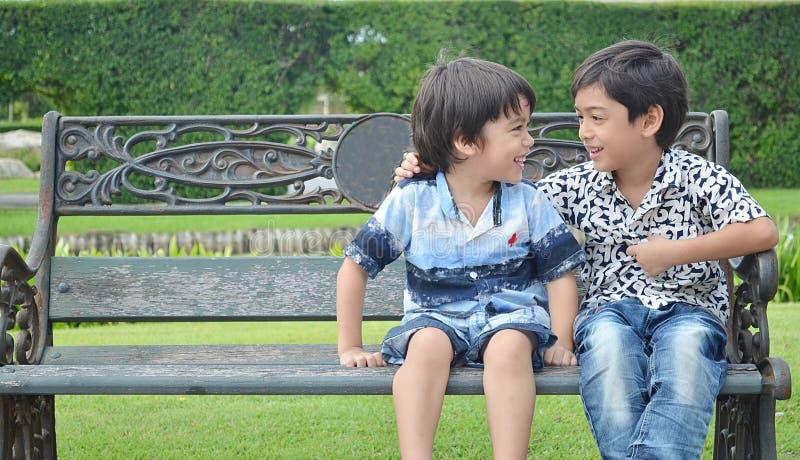 笑在庭院里的小兄弟姐妹男孩 库存照片