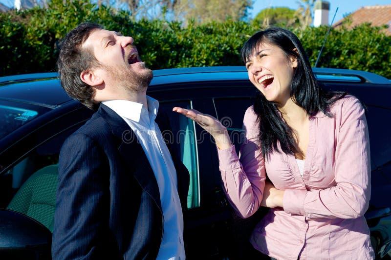 笑在汽车前面的愉快的成功的商人 免版税图库摄影