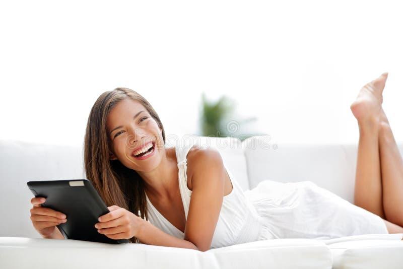 笑在沙发的片剂计算机的少妇 免版税库存照片