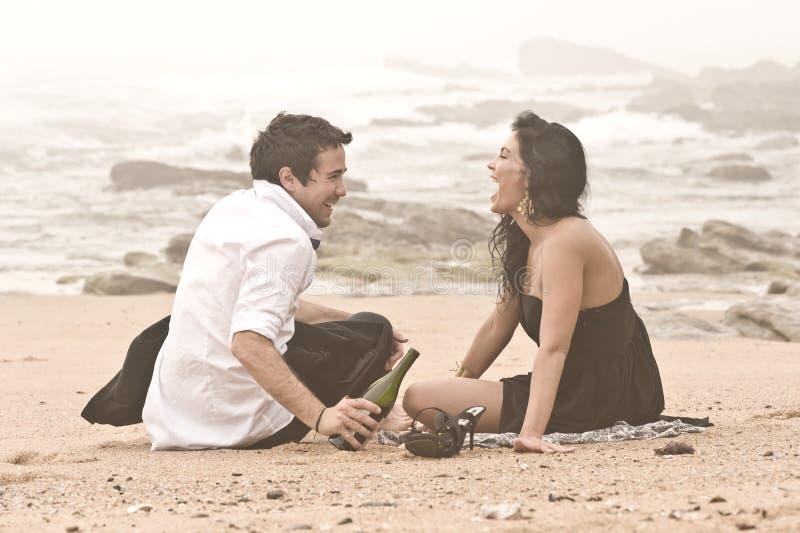 笑在海滩的年轻有吸引力的夫妇 图库摄影