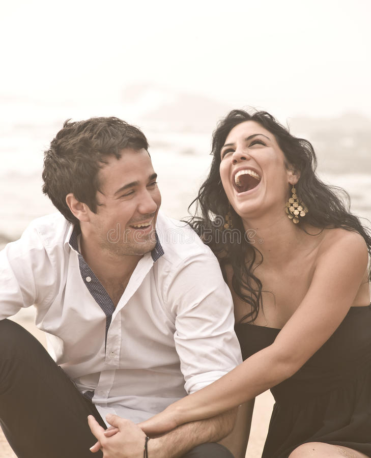 笑在海滩的年轻有吸引力的夫妇 免版税库存照片