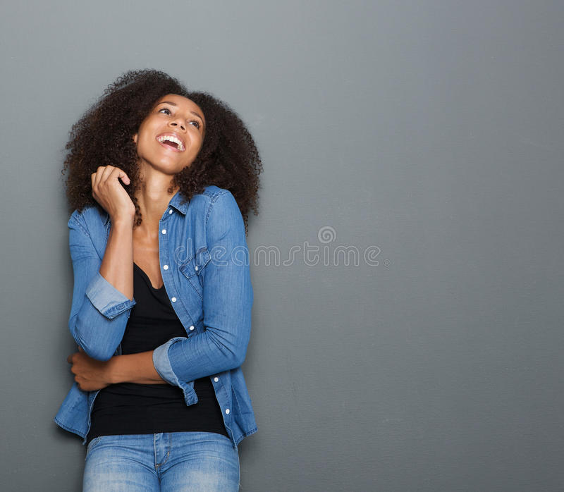 笑在灰色背景的年轻非裔美国人的妇女 免版税图库摄影