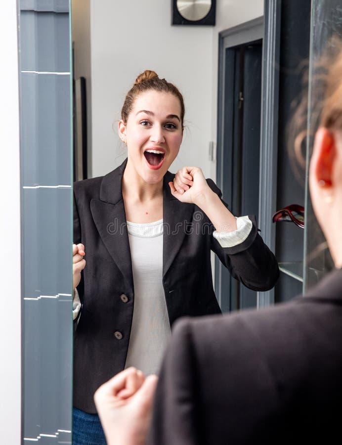 笑在镜子前面的惊奇的年轻美丽的女商人 库存照片