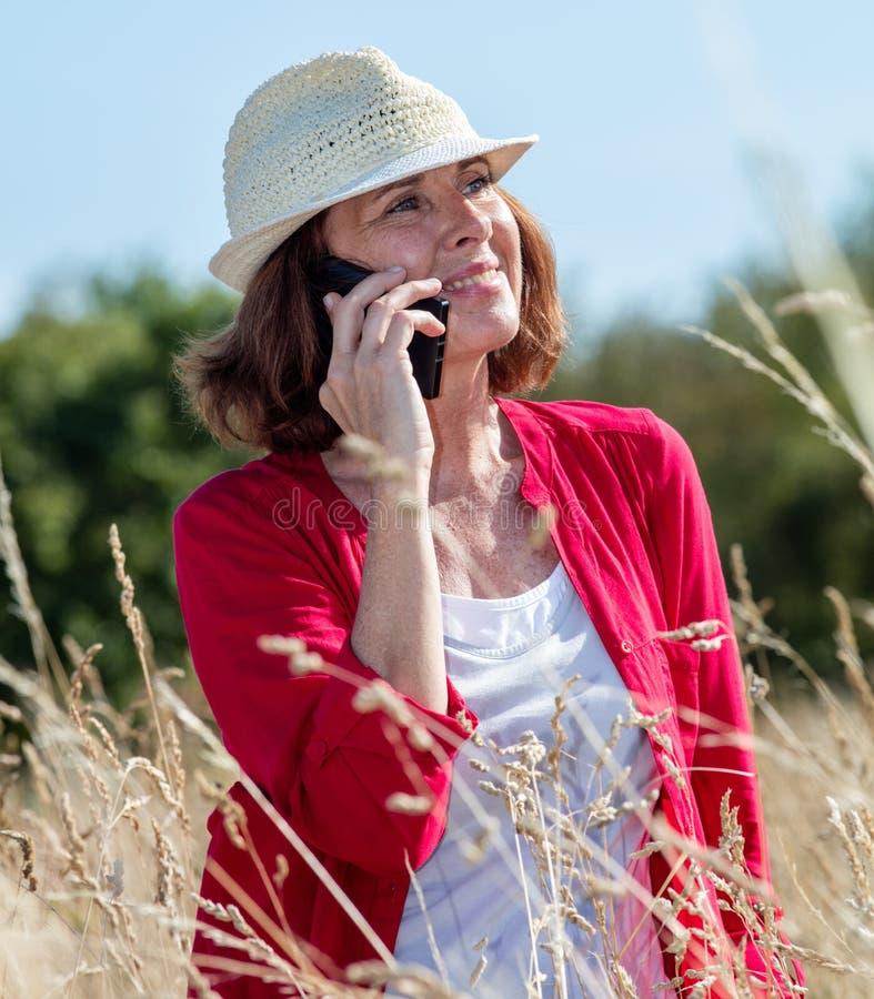 笑在高草地的电话的华美的成熟妇女 免版税库存照片