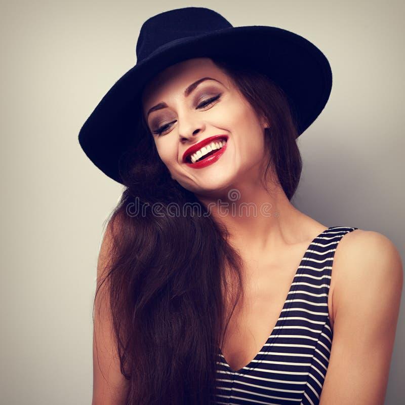 笑在黑典雅的帽子的愉快的构成女性模型 被定调子的c 库存照片