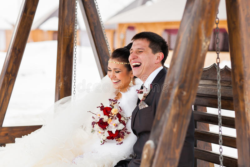 笑在他们的冬天婚礼之日的新娘和新郎 免版税库存图片