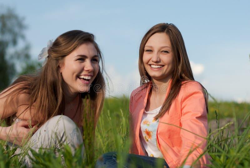 笑在绿草的两个青少年的女朋友 免版税库存图片