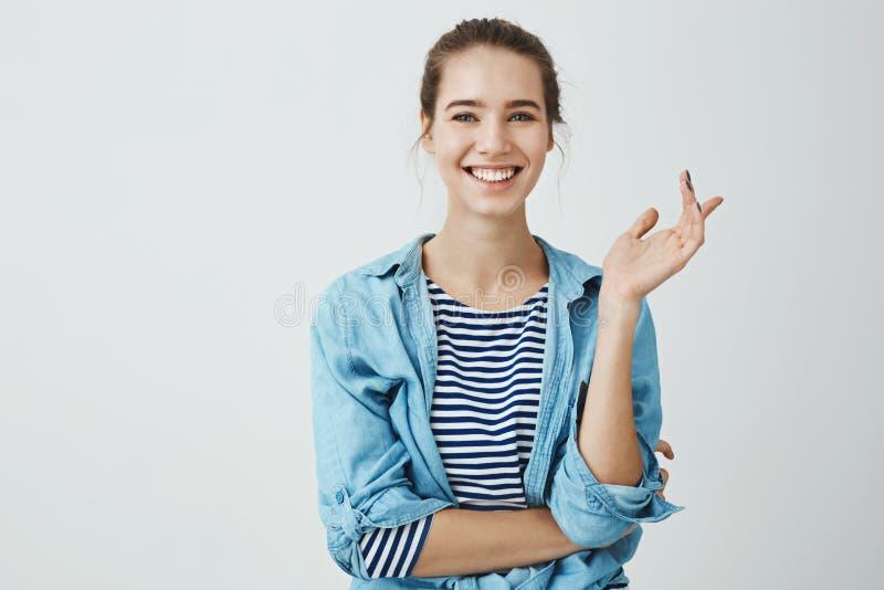 笑声缓解每天问题 时髦成套装备的打手势迷人的妇女有小圆面包发型的,当谈话与朋友时 库存图片