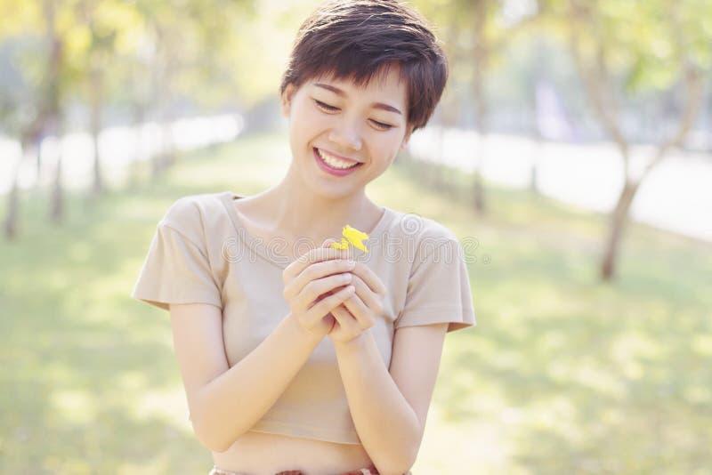 笑对小的花手中机智的年轻和美丽的妇女 库存图片