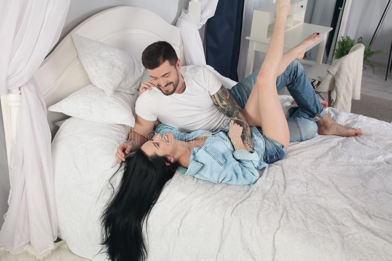 笑年轻的夫妇在床上和,当发痒时 免版税库存图片
