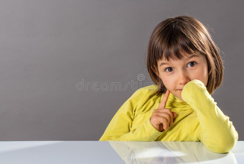 笑得脸皮脸颊的小女孩,表达了一个快乐的想法 免版税库存图片
