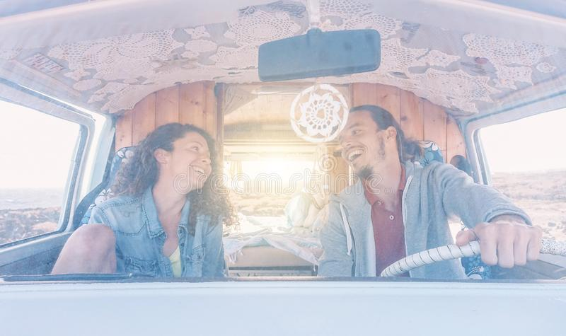 笑愉快的夫妇驾驶微型货车和,当看彼此-年轻人获得乐趣在一roadtrip期间在夏天时 免版税库存照片