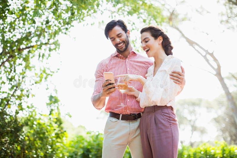 笑愉快的夫妇,当使用手机时 库存照片