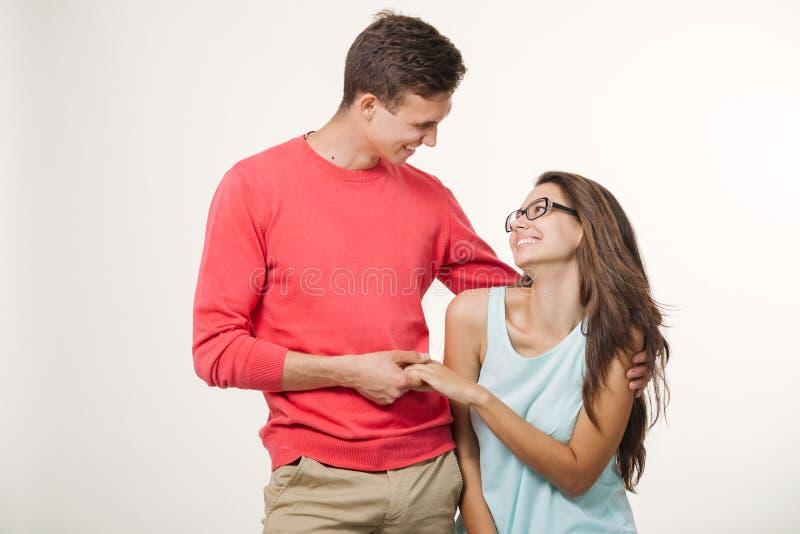 笑愉快的年轻可爱的夫妇一起站立和 工作室被射击在空白背景 友谊,爱和 库存图片