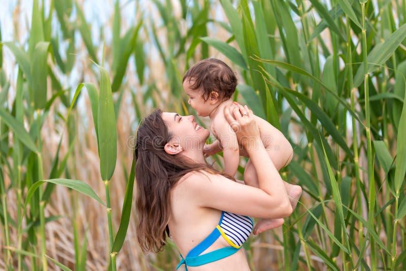 笑愉快的母亲拿着她的小女婴,他们使用和,夏时,在海海滩 库存图片
